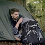 Male camper packs his rucksack while sat in the opening of a tent in the forest
